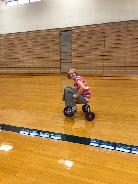 Mrs. Prentice teaching students to ride a tricycle